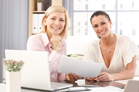 Happy casual blonde and brunette businesswomen at office working in front of laptop computer, checking business report papers, smiling, looking at camera. photo