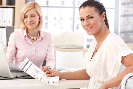 Happy smiling, brunette casual businesswoman working at office with business report in hand, looking at camera. photo