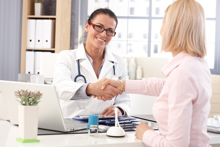 Happy female brunette doctor at medical office with patient, wearing glasses, stethoscope and lab coat. Shaking hands, smiling.