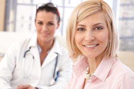 Close-up van happy blonde kaukasisch vrouwelijke patiënt bij de medische spreekkamer. Lachend en kijken naar de camera.