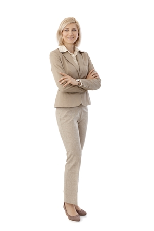 outspreading: Portrait of happy, blonde, caucasian secretary in beige suit. Smiling, looking at camera, arms crossed. Full size, white background. Stock Photo