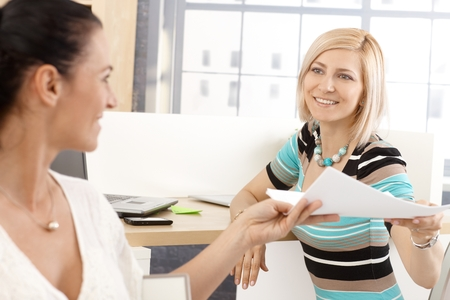 Blonde happy casual businesswoman working with colleague at office, smiling, handing over paperwork. photo
