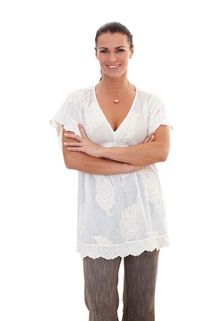 outspreading: Portrait of brunette, casual businesswoman standing with arms crossed, looking at camera, white background.