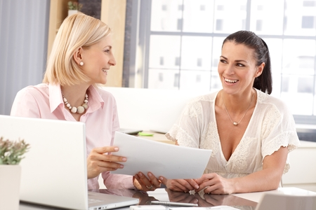 Happy casual businesswomen at office working in front of laptop computer checking business report papers, smiling. photo
