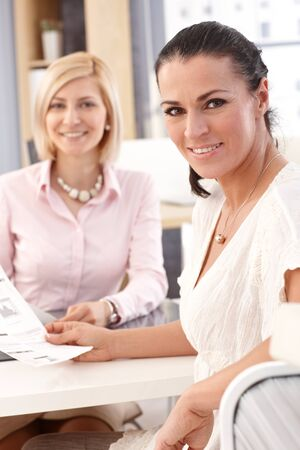 Close up of happy smiling, brunette casual female worker at office with business report in hand, looking at camera. photo