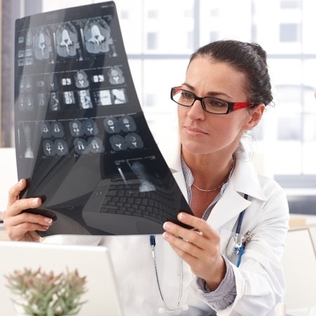 Portrait of female brunette doctor with x-ray image in hand, wearing glasses, stethoscope and lab coat, Standard-Bild