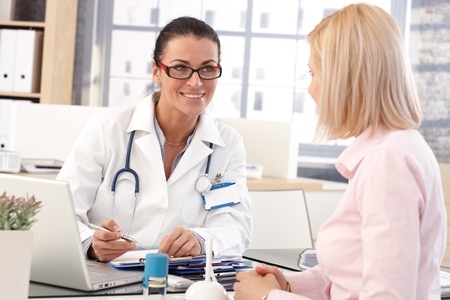 Happy female brunette doctor at medical office with patient, writing on clipboard, wearing glasses, stethoscope and lab coat.