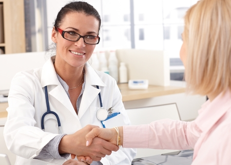 Close up of happy female brunette doctor at medical office with patient, wearing glasses, stethoscope and lab coat. Shaking hands, smiling. Standard-Bild