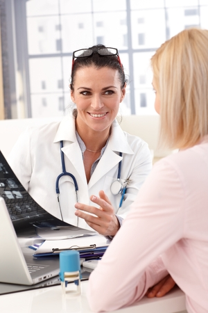 happy doctor woman: Close up of happy female brunette doctor with glasses at medical office with patient, smiling, x-ray image in hand, wearing stethoscope and lab coat. Stock Photo
