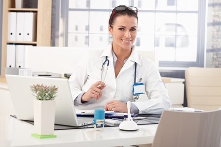Happy brunette caucasian female doctor sitting at medical office desk in front of laptop computer, wearing glasses, stethoscope and lab coat.