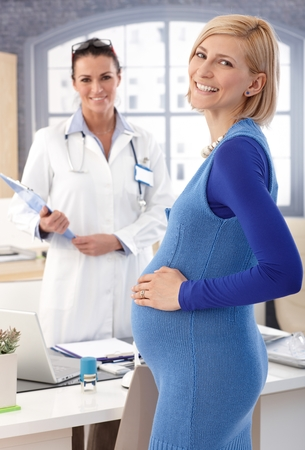 Happy, casual, caucasian blonde pregnant businesswoman standing at doctor's office. Hand on belly, smiling, side view, looking at camera. Stock Photo - 28345591