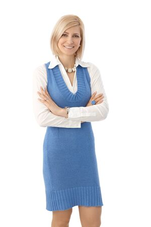 outspreading: Portrait of blonde, casual female office worker standing with arms crossed, looking at camera, white background. Looking at camera smiling. Stock Photo