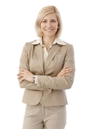 Porträt glücklich, blonde, kaukasisch Büroangestellte in beige Anzug. Lächeln, Blick in die Kamera, die Arme. Weiß Hintergrund.