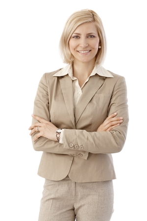 Portrait of happy, blonde, caucasian office worker in beige suit. Smiling, looking at camera, arms crossed. White background.
