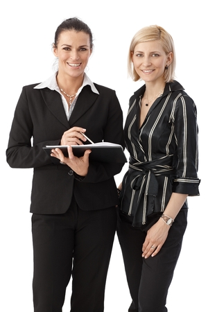 Group portrait of elegant happy caucasian, brunette and blonde office workers. Smiling, looking at camera, personal organizer in hand, white background. Stock Photo - 28345597