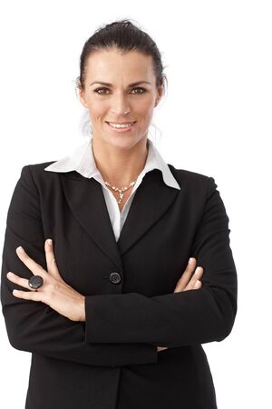 Close up portrait of happy brunette caucasian businesswoman wearing suit, standing in front of white background. Looking at camera, arms crossed, smiling. Stock Photo - 28345635
