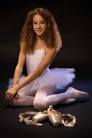 Pretty ballet student sitting on floor, smiling, looking at camera. photo