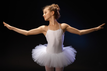 Young ballet student exercising over black background in tutu. photo