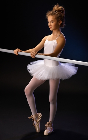 Ballet student in ballet costume practicing by ballet bar. photo