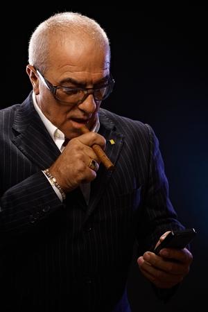 maffia: Portrait of maffia boss smoking cigar, using mobilephone. Stock Photo