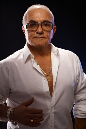 Portrait of old playboy in white shirt and lots of gold jewels. Stock Photo