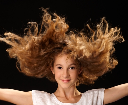 outspreading: Happy girl jumping with long curly hair, smiling, looking at camera. Closeup portrait.