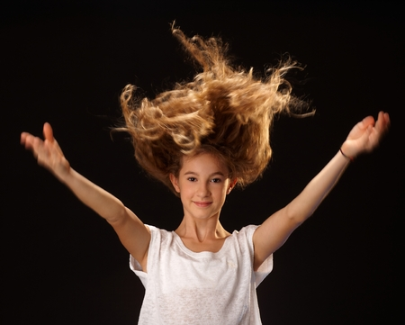 outspreading: Happy girl jumping with long curly hair, smiling, looking at camera, raising arms. Stock Photo
