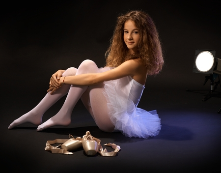 Pretty young ballet student sitting on floor, hugging legs, smiling, looking at camera, shoes lying next to her. photo