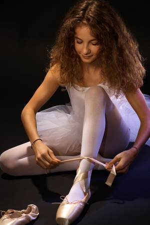 Pretty young ballet student tying lace on ballet shoe, sitting on floor. photo
