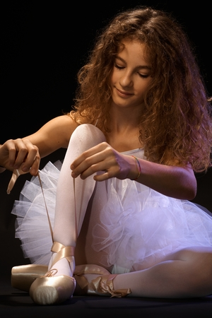 Young ballerina preparing herself for performance, tying lace on shoe. photo
