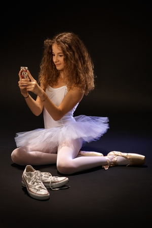 ballet slippers: Pretty ballet student using mobilephone, sitting on floor, smiling.