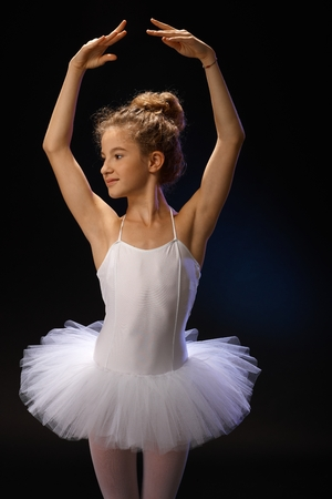 Pretty young ballet student posing front of black background, smiling, turning head right. photo