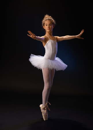 black toes: Pretty young ballet dancer standing on her toes, practicing over black background.