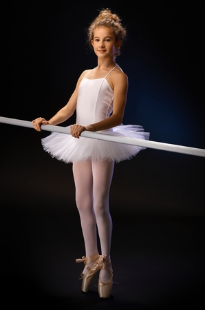 ballet bar: Ballet student practicing by ballet bar, standing on her toes. Full size over black background.