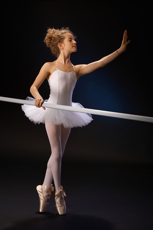 ballet bar: Young ballet student practicing classical ballet in classroom by ballet bar. Stock Photo