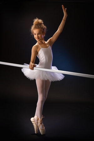 Young ballet student exercising by ballet bar over black background. Full size. photo