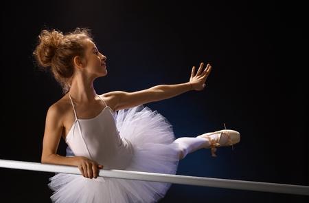 ballet bar: Young ballet dancer posing by ballet bar, stretching left leg, looking back.