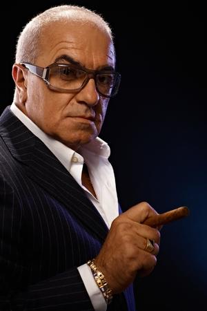 Closeup portrait of elegant mature man smoking cigar, looking serious.