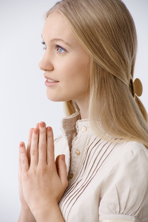 Innocent young woman praying. Side view. photo