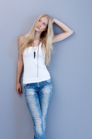 skiny: Pretty young blonde woman posing by wall in jeans and top.