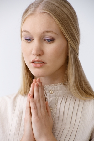 Young blonde woman praying, looking down. photo