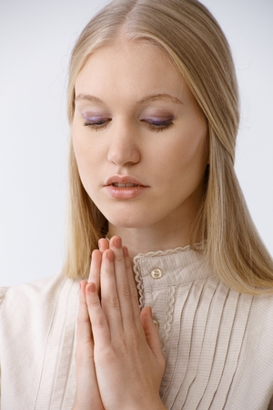 Young woman praying, looking down. photo