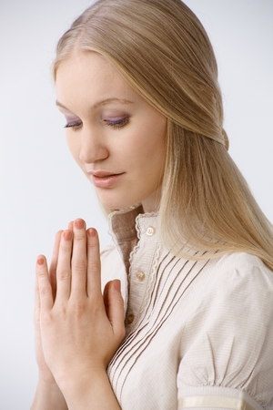 Portrait of young blonde woman praying, looking down. photo