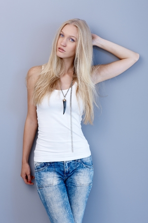 skiny: Young scandinavian beauty posing by wall, looking at camera, hand in hair. Stock Photo