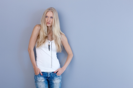 skiny: Casual nordic beauty in jeans and top posing by blue wall.
