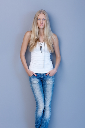 skiny: Beautiful young scandinavian woman standing against blue wall in jeans and top with hands in pockets, looking at camera serious.