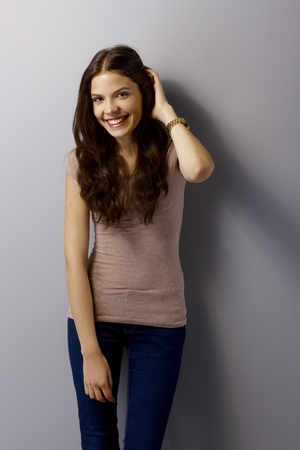 Happy young woman posing by grey wall, hand in hair. photo