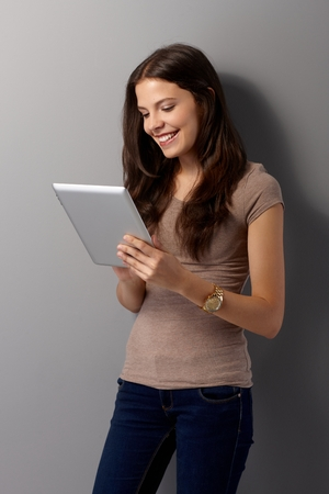 Happy young woman standing by grey wall, using tablet, smiling. photo