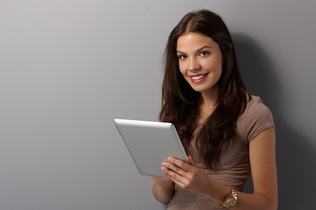 Happy young woman with long brown hair using tablet computer, smiling, looking at camera.