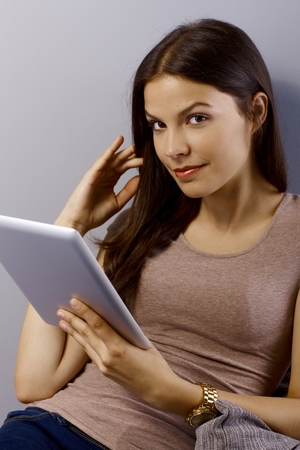 Attractive young woman using tablet, smiling, looking at camera. photo